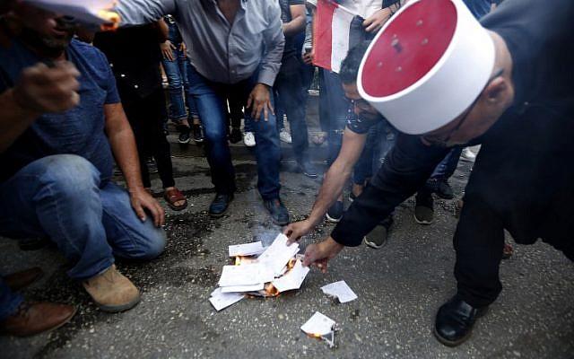 Les résidents du village druze de Majdal Shams dans le plateau du Golan, mettent le feu à de faux bulletins de vote, pour protester contre les élections municipales. le 21 ocotbre 2018. (Crédit : JALAA MAREY / AFP)