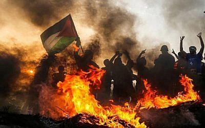 Un drapeau palestinien agité lors d'une émeute sur la plage le 22 octobre 2018, près de la frontière maritime avec Israël, dans le nord de la bande de Gaza. (Crédit : Mahmud Hams / AFP)