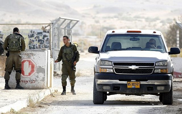Un soldat israélien inspecte une voiture qui revient d'une plantation de poivrons au moshav Tsofar, à la frontière israélo-jordanienne, le 23 ocotbre 2018. (Crédit : JACK GUEZ / AFP)