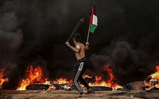 Un Palestinien tient un drapeau palestinien alors qu'il utilise une fronde pour lancer des pierres sur les troupes israéliennes lors d'affrontements près de la frontière avec Israël, à l'est de Gaza City, le 26 octobre 2018. (Crédit : Mahmud Hams / AFP)