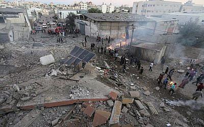 Des Palestiniens rassemblés autour des décombres d'un bâtiment de la ville de Gaza détruit par une frappe aérienne israélienne le 27 octobre 2018. (Crédit : Mahmud Hams / AFP)