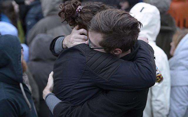 Des membres de la communauté de Squirrel Hill s'embrassent lors d'une vigile organisée par des étudiants en souvenir de ceux qui sont morts plus tôt dans la journée lors d'une fusillade à la synagogue Tree of Life dans le quartier de Squirrel Hill à Pittsburgh le 27 octobre 2018. (Crédit : Dustin Franz / AFP)