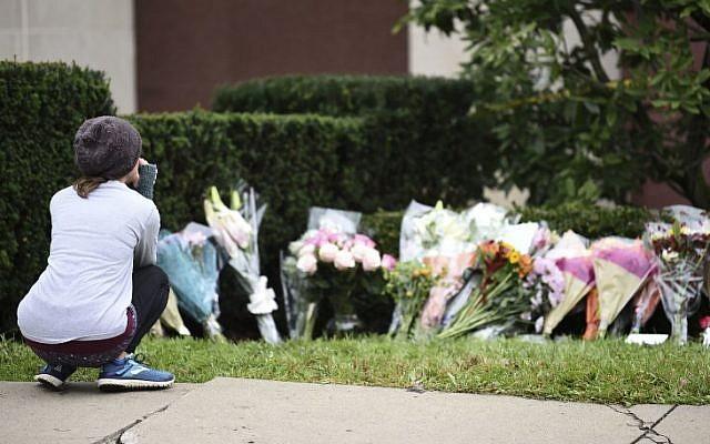 Une femme regarde les fleurs d'un mémorial aux abords de la synagogue Tree of Life de Pittsburgh, aux Etats-Unis, au lendemain d'une fusillade meurtrière, le 28 octobre 2018 (Crédit : Brendan SMIALOWSKI/AFP)