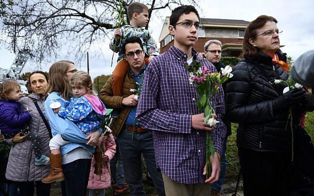 Des gens rendent un dernier hommage à un mémorial dressé en souvenir des onze  victimes d'une fusillade survenue le 27 octobre dans la synagogue Tree of life de Pittsburgh, dans le quartier de Squirrell Hill, le 28 octobre 2018 (Crédit :  Brendan Smialowski / AFP)