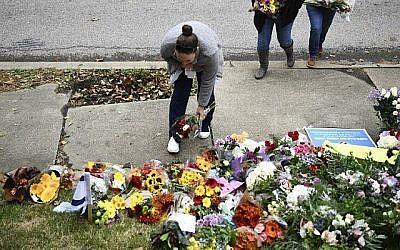 Une femme dépose des fleurs devant la synagogue Tree of life, du quartier de Squirell Hill, à Pittsburgh, après un attentat la veille dans unes synagogue qui a fait 11 morts, le 28 octobre 2018. (Crédit ! Brendan Smialowski / AFP)