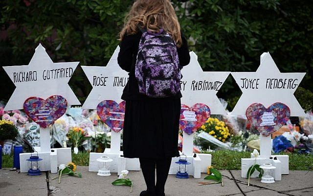Une femme se recueille devant un mémorial pour les victimes de la fusillade mortelle dans la synagogue Tree of Life, dans le quartier Squirrel Hill de Pittsburgh, le 27 octobre. (SMIALOWSKI/AFP)