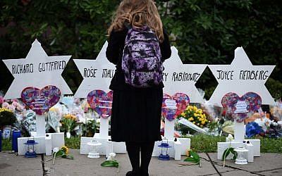 Une femme se tient devant le mémorial érigé en hommage aux victimes de la fusillade de la synagogue Tree of life, à Pittsburgh, (Crédit : Brendan SMIALOWSKI / AFP)