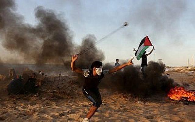 Un Palestinien jette des pierres sur des soldats israéliens lors d'une émeute sur la plage près de la frontière maritime avec Israël, à Beit Lahia, dans le nord de la bande de Gaza, le 29 octobre 2018. (MAHMUD HAMS / AFP)