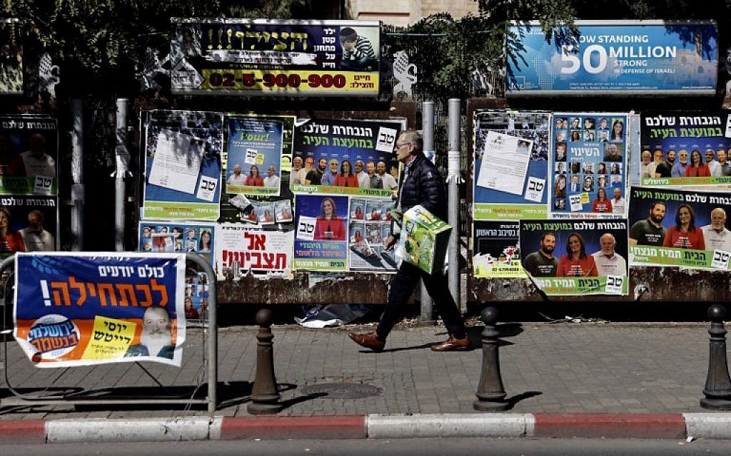 Un Israélien accroche des affiches de campagne pour les élections locales dans le centre de Jérusalem le 30 octobre 2018. (Crédit : THOMAS COEX / AFP)