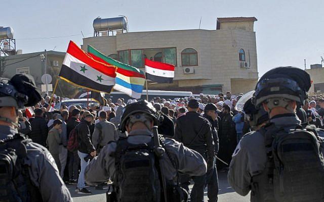 Les forces de sécurité israéliennes montent la garde pendant que les hommes druzes protestent contre les élections municipales devant un bureau de vote dans le village de Majdal Shams, le 30 octobre 2018. (Crédit : JALAA MAREY / AFP)