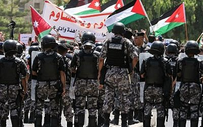 Les forces de sécurité jordaniennes montent la garde alors que les manifestants brandissent des drapeaux jordaniens et scandent des slogans lors d'une manifestation aux abords de l'ambassade israélienne, à Amman, le 28 juillet 2017. (Crédit : AFP Photo/Khalil Mazraawi)