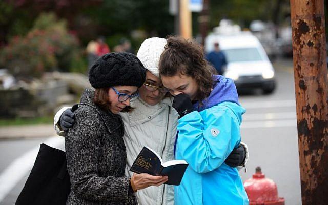 Tammy Hepps, Kate Rothstein et sa fille de 16 ans Simone Rothstein, prient aux abords du site d'une fusillade meurtrière à la synagogue Tree of Life du quartier Squirrel Hill à Pittsburgh, Pennsylvanie, le 27 octobre 2018 (Crédit : Jeff Swensen/Getty Images/AFP)