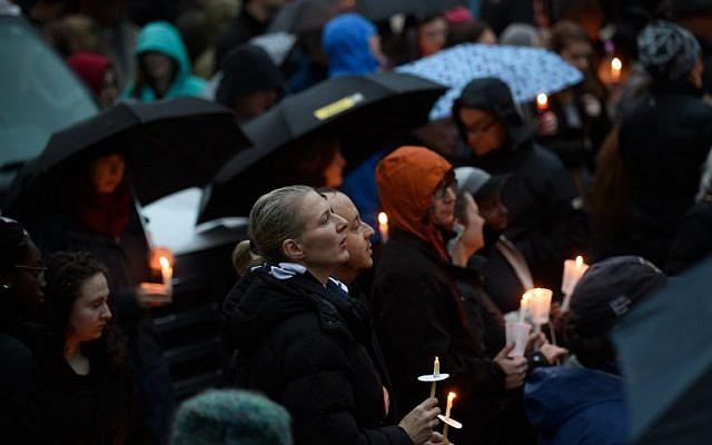Les gens se réunissent pour une veillée interconfessionnelle à quelques blocs d'immeubles du site d'une fusillade de masse survenue à la synagogue Tree of Life de Pittsburgh, en Pennsylvanie, le 27 octobre 2018 (Crédit : Jeff Swensen/Getty Images/AFP)