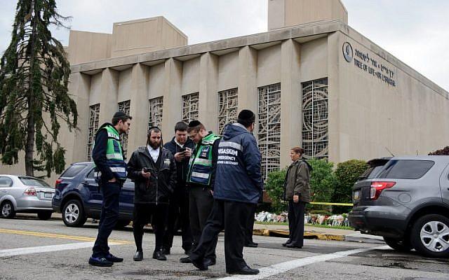 """Une équipe d'urgence juive et des policiers sur les lieux de la fusillade de masse qui a tué 11 personnes et en a blessé six à la synagogue """"Tree Of Life"""", le 28 octobre 2018, à Pittsburgh, Pennsylvanie. (Crédit : Jeff Swensen/Getty Images/AFP)"""