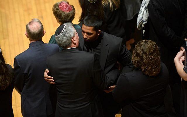 Wasi Mohamed, directeur exécutif du Centre islamique de Pittsburgh, est pris dans les bras par un rabbin après s'être adressé à l'auditoire au cours d'une cérémonie en l'honneur des victimes de la fusillade de samedi à la synagogue Tree Of Life. (Crédit : Jeff Swensen / Getty Images / AFP)