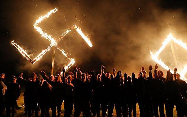 Illustration : des membres du Mouvement national socialiste, l'un des plus grands groupes néonazis aux États-Unis, brûlent une croix gammée après un rassemblement le 21 avril 2018 à Draketown, en Géorgie. (Crédit : Spencer Platt / Getty Images / AFP)