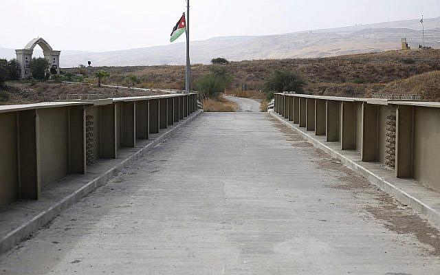 Un drapeau jordanien pendu sur un pont menant d'Israël à la Jordanie, sur le site de Naharayim, ou Baqura en arabe, dans la vallée du Jourdain, le 22 octobre 2018 (Crédit :  AP Photo/Ariel Schalit)