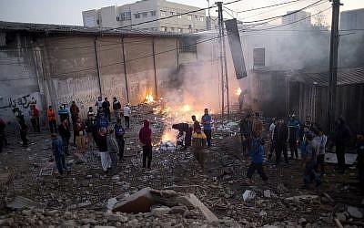 Les Palestiniens vérifient les dégâts causés aux bâtiments détruits par les frappes aériennes israéliennes à Gaza le 27 octobre 2018 après des tirs de roquettes depuis Gaza. (Crédit : AP / Khalil Hamra)
