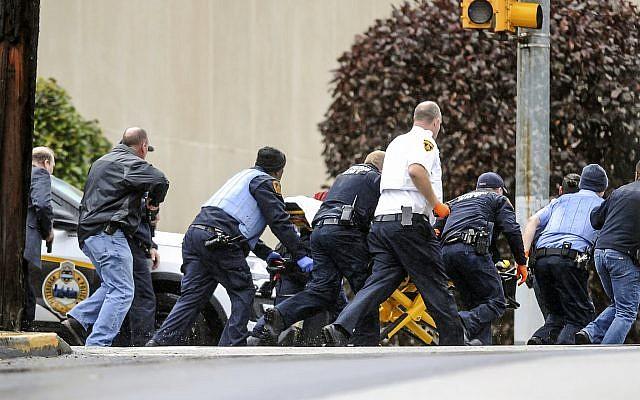 Les forces de l'ordre ont conduit une personne sur une civière sur le lieu de la fusillade où plusieurs personnes ont été tuées par balle, le samedi 27 octobre 2018, dans la synagogue Tree of Life dans le quartier de Squirrel Hill à Pittsburgh. (Crédit : Alexandra Wimley / Pittsburgh Post-Gazette via AP)