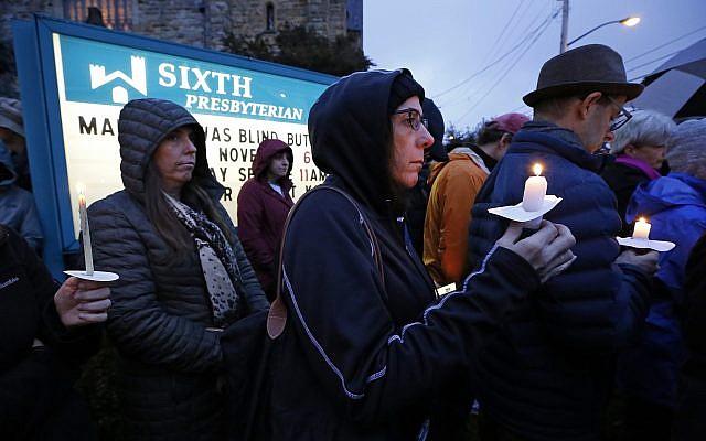 Une foule avec des bougies sur la pelouse de la sixième église presbytérienne à l'intersection de Murray Ave. et Forbes Ave. dans le quartier de Squirrel Hill à Pittsburgh, en Pennsylvanie, lors de la veillée commémorative en l'honneur des victimes de la fusillade dans la synagogue Tree of life, où un homme armé a tué 11 fidèles dans la journée du samedi 27 octobre 2018. (Crédit : AP Photo / Gene J. Puskar)