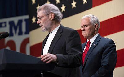 """Le vice-président Mike Pence, à droite, prie avec le """"rabbin"""" Loren Jacobs, pour les victimes de la fusillade de la synagogue de Pittsburgh lors d'un rassemblement républicain à Waterford, dans le Michigan (Crédit : Tanya Moutzalias/Ann Arbor News-MLive.com via AP)"""