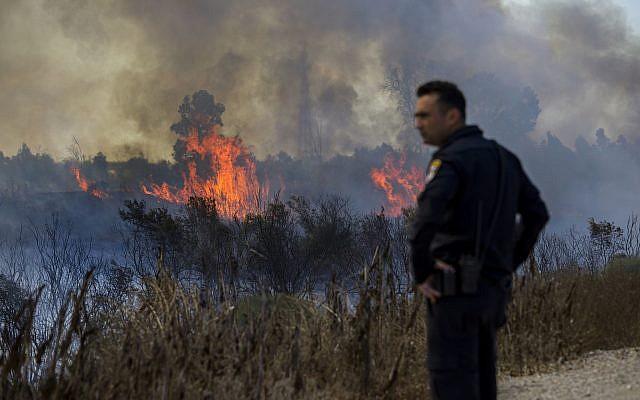 Un policier israélien regarde un incendie déclenché par un ballon transportant un tissu en feu, lancé par des Palestiniens de la bande de Gaza dans la réserve naturelle de Karmia, le jeudi 11 octobre 2018 (Crédit : AP/Tsafrir Abayov)