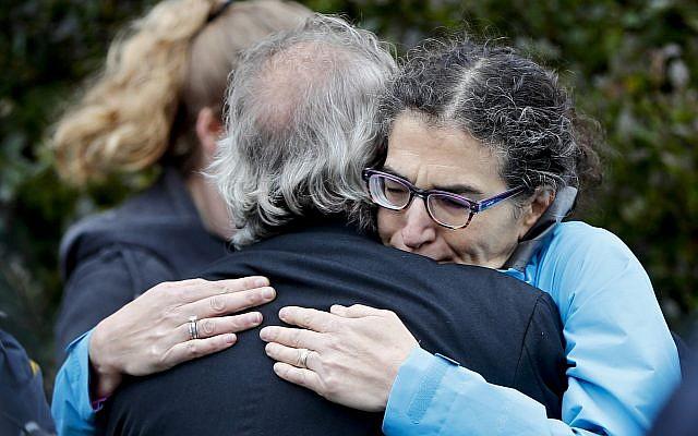 Des gens se réconfortent dans le quartier Squirrel Hill de Pittsburgh après une fusillade survenue à la synagogue Tree of Life le 27 octobre 2018 (Crédit : AP/Keith Srakocic)