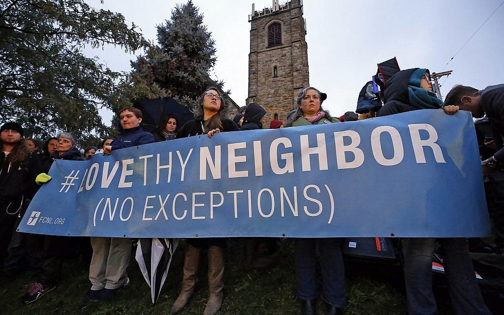 Un groupe tient une pancarte à l'intersection de Murray Ave. et Forbes Ave. dans le quartier de Squirrel Hill à Pittsburgh lors d'une veillée commémorative en l'honneur des victimes de la fusillade de la synagogue de Tree of life, où un tireur a ouvert le feu, faisant 11 morts et six blessés, dont quatre policiers, samedi 27 octobre 2018. (Crédit : AP Photo / Gene J. Puskar)