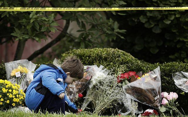 Gideon Murphy place des fleurs aux abords de la synagogue Tree of Life de Pittsburgh, aux Etats-Unis, au lendemain d'une fusillade meurtrière, le 28 octobre 2018 (Crédit : AP Photo/Matt Rourke)