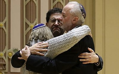 Le rabbin Jeffrey Myers, à droite, de la congrégation Tree of Life/Or L'Simcha étreint le rabbin Cheryl Klein, à gauche, de la congrégation Dor Hadashet le rabbin  Jonathan Perlman pendant un rassemblement organisé suite à la fusillade meurtrière de la synagogue Tree of Life à  Pittsburgh, le 28 octobre 2018 (Crédit :  AP Photo/Matt Rourke)