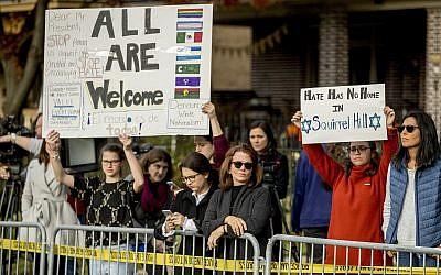 Des manifestants brandissent des pancartes alors que le président Donald Trump et la first lady Melania Trump visitent la synagogue Tree of Life de  Pittsburgh, le mardi 30 octobre 2018 (Crédit : AP Photo/Andrew Harnik)