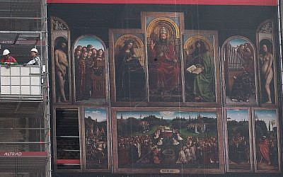 Des ouvriers dans une nacelle à côté de la reproduction géante de l'oeuvre de 'l'Adoration de l'Agneau mystique' du peintre flamand Jan van Eyck pendant la rénovation de la cathédrale Saint-Bavo de Gand, en Belgique, le 13 mars 2014 (Crédit : AP Photo/Yves Logghe)