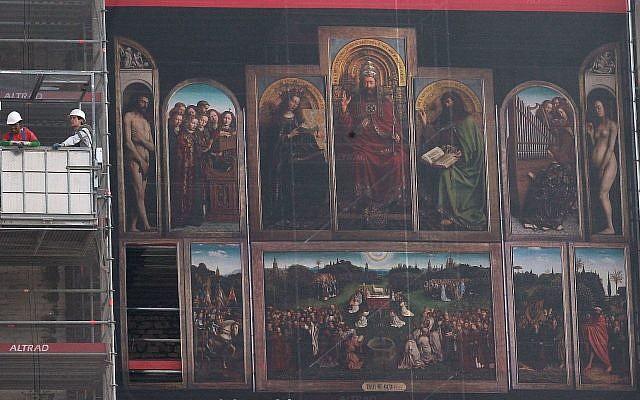 Des ouvriers dans une nacelle à côté de la reproduction géante de l'oeuvre de 'l'Adoration de l'Agneau mystique' du peintre flamand Jan van Eyck pendant la rénovation de la cathédrale Saint-Bavo de Gand, en Belgique, le 13 mars 2014 (Crédit : AP Photo/Yves Logghe)