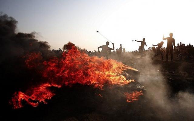 Des Palestiniens lancent des pierres en direction des forces israéliennes lors d'affrontements à la frontière entre Israël et la bande de Gaza, à l'est de la ville de Gaza, le 28 septembre 2018. (Photo AFP / Said Khatib)