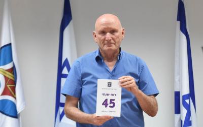 Le 28 mai 2017, le médiateur de Tsahal, Yitzhak Brick, pose avec une copie de son rapport annuel. (ministère de la défense)