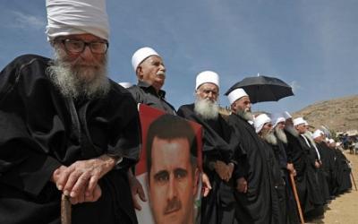 Des membres de la communauté druze tenant le portrait du président syrien Bashar el-Assad lors d'un rassemblement dans le village druze de Majdal Shams dans les hauteurs du Golan israélien, le 6 octobre 2018, commémorant le 45e anniversaire de la guerre israélo-arabe de 1973. (AFP PHOTO / JALAA MAREY)