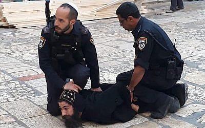 Des officiers de police israéliens retiennent un clerc copte lors d'une manifestation contre des travaux dans l'église du Saint-Sépulcre dans la Vieille Ville de Jérusalem, le 24 octobre 2018. (Crédit : patriarcat des Coptes orthodoxes à Jérusalem / Facebook)