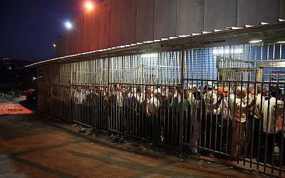 Des travailleurs palestiniens attendent à un check point à la barrière de sécurité, dans la ville de Bethléem, en Cisjordanie, le 23 août 2010 (Crédit : Najeh Hashlamoun/Flash 90)