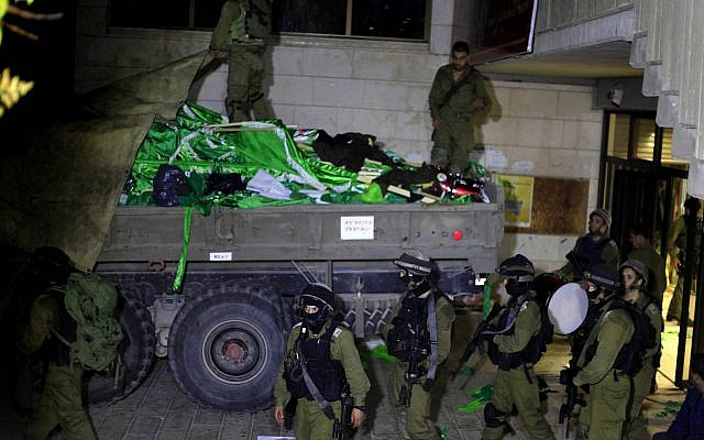 Des soldats israéliens sont en train de charger des drapeaux du Hamas lors d'une patrouille à l'Université de Birzeit, à la périphérie de la ville de Ramallah, en Cisjordanie, lors d'une opération le 19 juin 2014. (Issam Rimawi/Flash90)