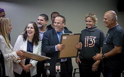 Le ministre des Communications Ayoub Kara avec des représentants des chaînes Reshet (à droite) et Keshet (à gauche) durant une cérémonie de remise des licences pour les nouvelles 12ème et 13ème chaîne à Jérusalem, suite à la scission de la Deuxième chaîne, le 31 octobre 2017 (Crédit : Yonatan Sindel/Flash90)
