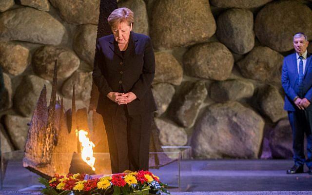La chancelière allemande Angela Merkel dépose une couronne au cours d'une cérémonie dans la salle du souvenir du mémorial de la Shoah Yad Vashem à Jérusalem, le 4 octobre 2018 (Oren Ben Hakoon/POOL)