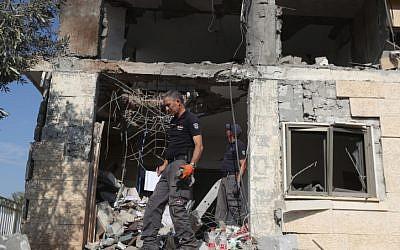 Les forces de sécurité israéliennes inspectent une maison frappée par une roquette lancée depuis la bande de Gaza à Beer Sheva, dans le sud d'Israël, le 17 octobre 2018 (Crédit : Yonatan Sindel/Flash90)
