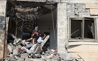 Les forces de sécurité israéliennes inspectent un bâtiment qui a été touché par une roquette tirée depuis la bande de Gaza dans la ville de Beer Sheva dans le sud d'Israël, le 17 octobre 2018. (Yonatan Sindel/Flash90)