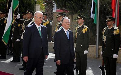 Le vice-président chinois Wang Qishan et le Premier ministre de l'Autorité palestinienne Rami Hamdallah traversent une haie d'honneur dans la ville de Ramallah, en Cisjordanie, le 23 octobre 2018 (Crédit :  Flash90)