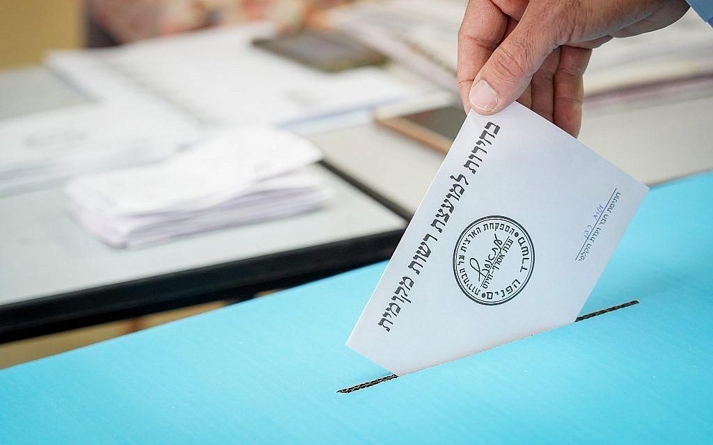 Un homme dépose son bulletin de vote dans un bureau de vote le matin des élections municipales du 30 octobre 2018 à Kedumim. (Crédit : Hillel Maeir / Flash90)