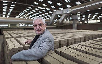 Jacques Grishaver, président de la commission d'Auschwitz des Pays-Bas, inspecte les briques fabriquées en 2016 dans la ville néerlandaise de Nijmegen qui porteront les noms des survivants de la Shoah et qui seront incorporées dans un monument à Amsterdam, actuellement au stade de la proposition (Crédit : Marcel Molle/via JTA)