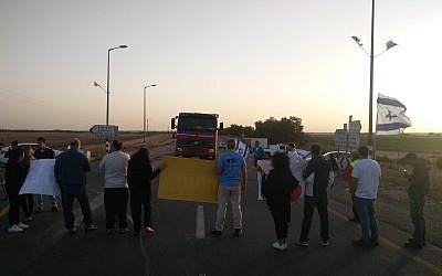 Les résidents du sud et des militants de l'organisation Im Tirtzu empêchent un camion d'entrer à Gaza, le 29 octobre 2018. (Crédit : Im Tirtzu)