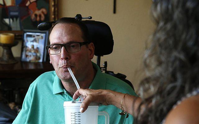 Un homme atteint de sclérose en plaques boit, aidé par une femme, le 21 août 2018 (Crédit : AP Photo/Brennan Linsley)