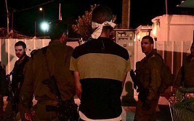 Les soldats israéliens arrêtent l'auteur présumé d'un attentat à l'arme blanche commis contre un soldat réserviste aux abords d'une base de l'armée israélienne dans le nord de la Cisjordanie, le 12 octobre 2018 (Crédit : Nasser Ishtayeh/Flash90)