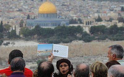 Le Dôme du Rocher dans la Vieille Ville de Jérusalem sert de toile de fond à un guide touristique qui présente une image de l'ancien Temple Juif. (Nati Shohat/FLASH90)